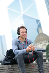 Urban man on smart phone wearing headphones