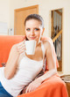 Portrait of   girl on  couch with  cup of tea.