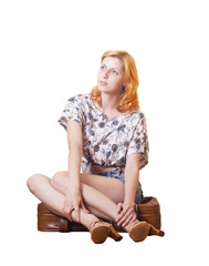 girl sitting on a suitcase on a white background isolated