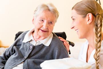Pflegerin bringt Handtücher zu Seniorin im Heim