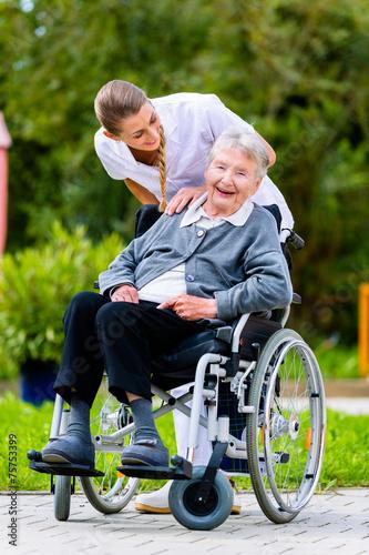 Leinwanddruck Bild Altenpflegerin schiebt Seniorin im Rollstuhl