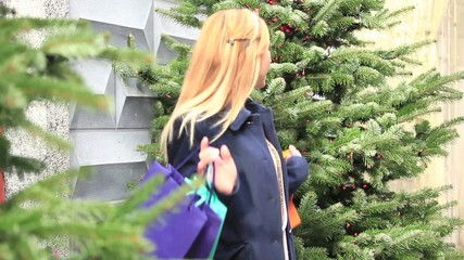 Woman getting out of shop with shopping bags-Christmas time