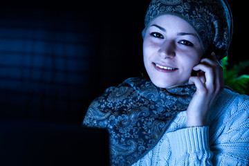 Smiling Middle Eastern Woman with Computer and Headset at Night