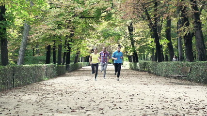 Young people jogging in park during autumn