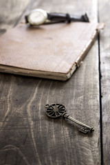 old book and a brass key on a vintage surface