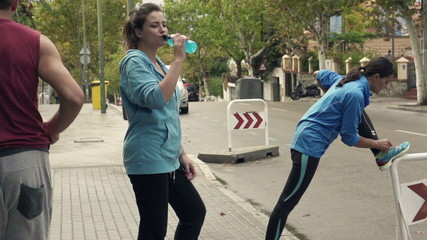 Young people stretching, drinking and jogging in city