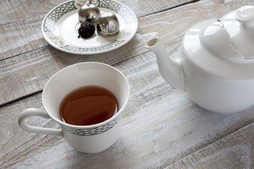 Red tea, teapot and tea ball infuser on table