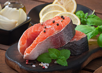 Fresh and raw steaks trout on a wooden cutting board