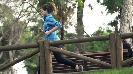 Beautiful, young woman jogging in park during autumn,