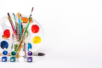 isolated paint pallette and paints brushes in glass