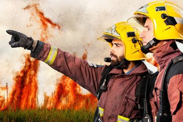 Firemen indicating fire to companion.