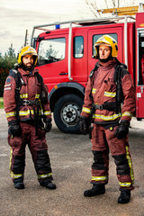 Firemen standing next to fire truck.