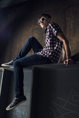 young man sitting over industrial background