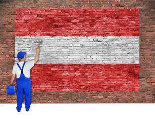 House painter covers brick wall with flag of Austria