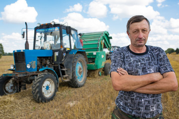 Farmer standing in front of tractor hay bale maker farm machine