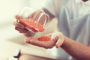 close up of male emptying jar with red lentils
