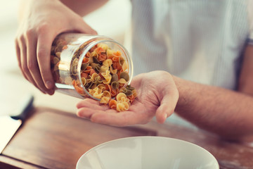 close up of male emptying jar with colorful pasta