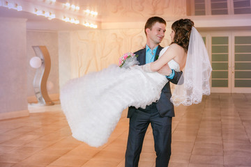 Kiss and dance young bride and groom in banqueting hall