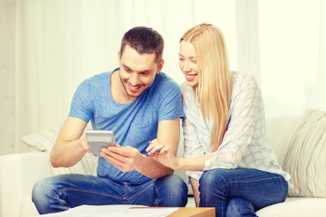 smiling couple with papers and calculator at home