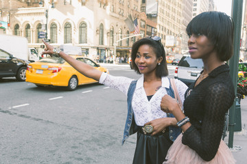 Two Beautiful Black Woman Calling a Taxi in New York