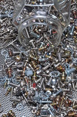 Set of bolts screws and nuts with the glass jar