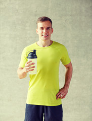 smiling man with protein shake bottle