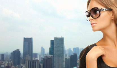 beautiful woman in shades over city background