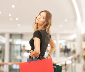 young happy woman with shopping bags in mall