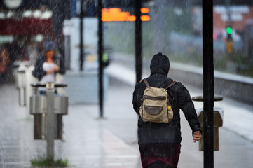 Woman in raincoat in heavy rain on train station platform