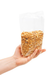 Oatmeal flakes into hand. Isolated on a white background.