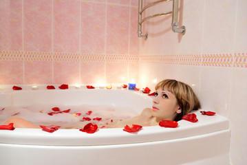 A girl takes a bath in the foam