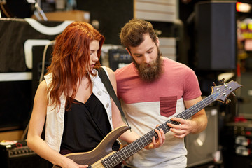 musicians playing bass guitar at music store