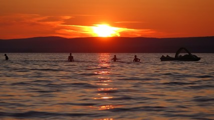 Happy bathers in the Balaton lake at a beauty summer sunset