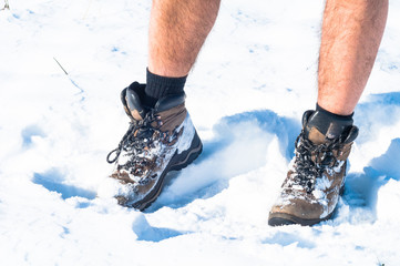 Hiking shoes covered in snow. Focus on shoes and man legs.