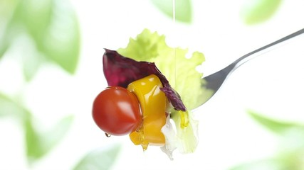 fork lettuce salad leaves, tomato and pepper topped with olive o