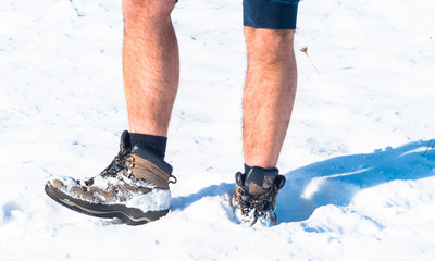 Man walking in a field covered in snow. Focus on shoes and legs