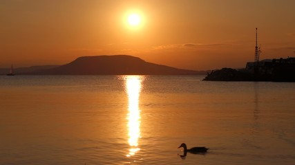 Sunset on Balaton lake with a catamaran boat comes into port