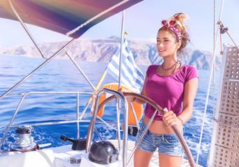 Beautiful woman behind helm of sailboat