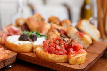 Italian appetizers on wooden plank