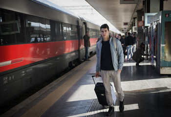 Handsome young male traveler in train station