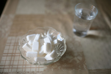 Sugar cubes and glass of water