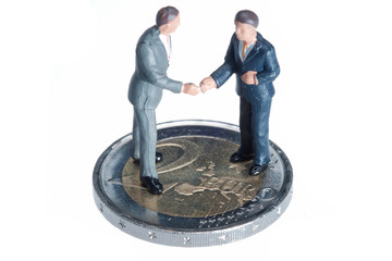 Two miniature businessmen on a two euros coin isolated on white