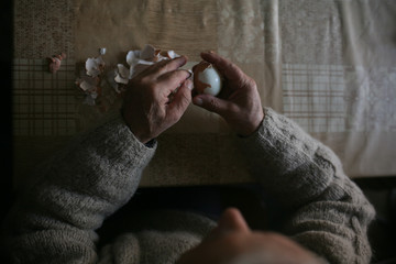 Old man peeling eggs