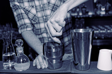 Barman is muddling cocktail ingredients in shaker, toned