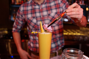 Bartender is decorating a cocktail with mango