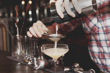 Bartender is straining drink in a glass