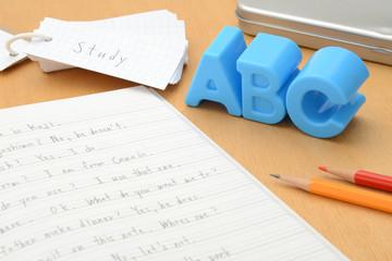 机の上の英語のノートとアルファベットのおもちゃ