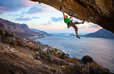 Rock climber on overhanging cliff before sunset