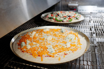 Cheese pizza entering the industrial oven