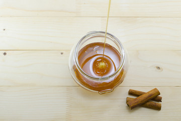 Honey dripping into a glass jar